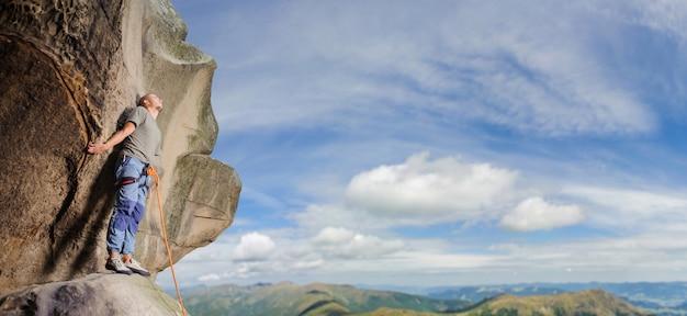 Männlicher bergsteiger, der großen flussstein in der natur mit seil klettert