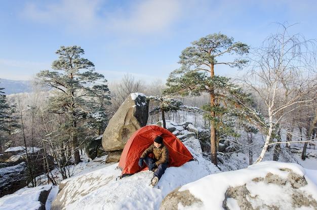 Männlicher bergsteiger fast sein zelt auf felsen
