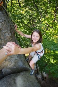Männlicher bergsteiger hilft einem jungen schönen weiblichen bergsteiger, eine spitze des berges zu erreichen