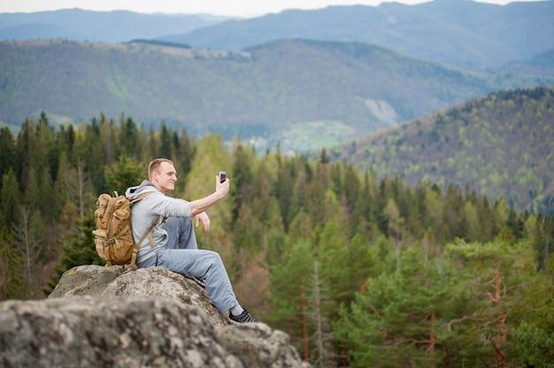 Männlicher bergsteiger mit braunem rucksack auf der spitze des felsens