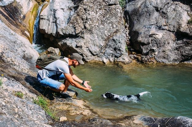 Männlicher besitzer von spaniel-hund, der gegen berge und wasserfallhintergrund geht