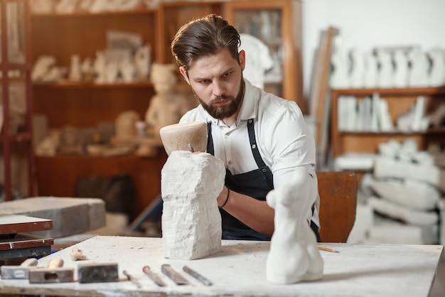 Männlicher bildhauer im weißen hemd und in der schwarzen schürze macht eine kalksteinkopie des frauentorsos im künstlerischen atelier.