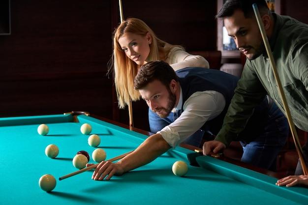 Männlicher billardspieler, der die beste lösung und den richtigen winkel beim billard- oder snooker-pool-sportspiel findet, ist konzentriert