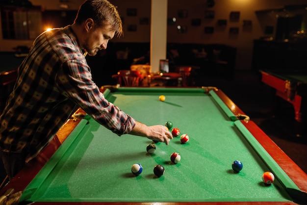 Männlicher billardspieler legt bälle auf grünen tisch, poolrauminnenraum. mann spielt amerikanisches poolspiel in der sportbar