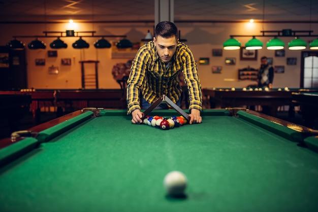 Männlicher billardspieler mit pyramide legt bunte kugeln auf grünen tisch.