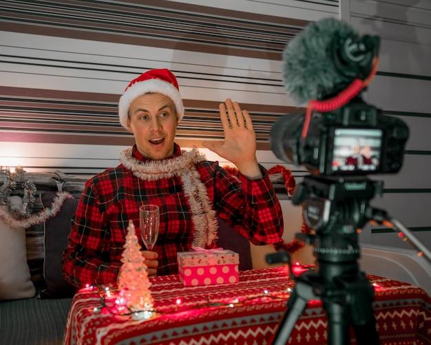 Männlicher blogger mit weihnachtsgeschenken vor feiertagen