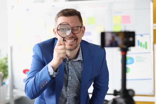 Männlicher blogger schaut durch die lupe in die kamera. suche nach neuen ideen für startup-konzept