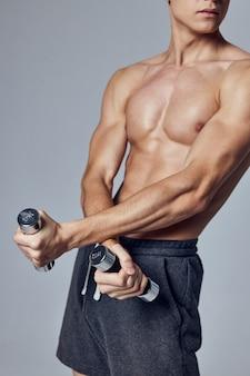 Männlicher bodybuilder, der hanteln hält, übt gymnastikstärke aus