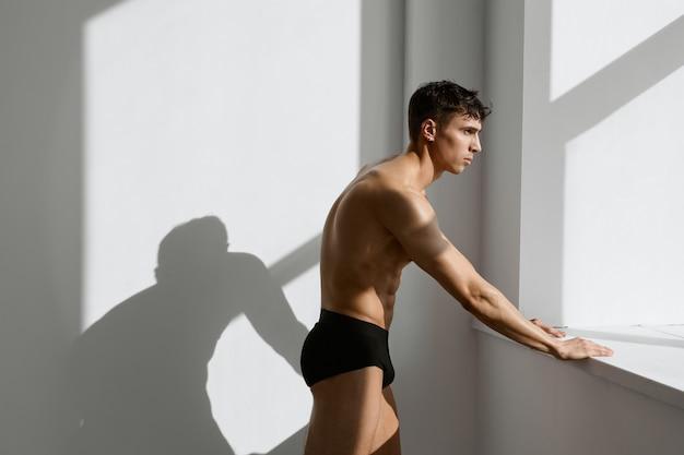 Männlicher bodybuilder in schwarzen shorts posiert am fenster
