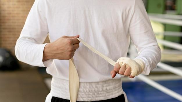 Männlicher boxer, der seine hände mit schutzband einwickelt