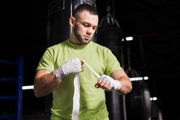 Männlicher boxer im t-shirt, das auf schutz für hände sich setzt