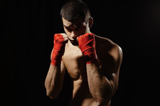 Männlicher boxer-kämpfer, der in der selbstbewussten defensiven haltung mit den händen in den verbänden oben aufwirft