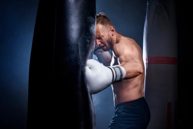 Männlicher boxer mit boxsack während des trainings