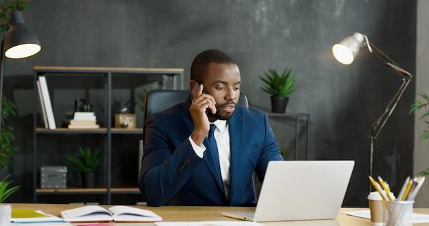 Männlicher büroangestellter der afroamerikaner, der am tisch sitzt und auf smartphone spricht, während er am laptop arbeitet.