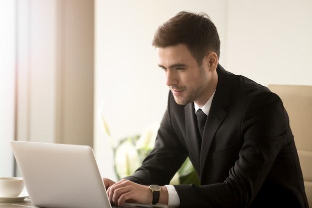 Männlicher büroangestellter, der an laptop im büro arbeitet