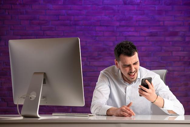 Männlicher büroangestellter der vorderansicht, der hinter seinem arbeitsplatz sitzt und spricht