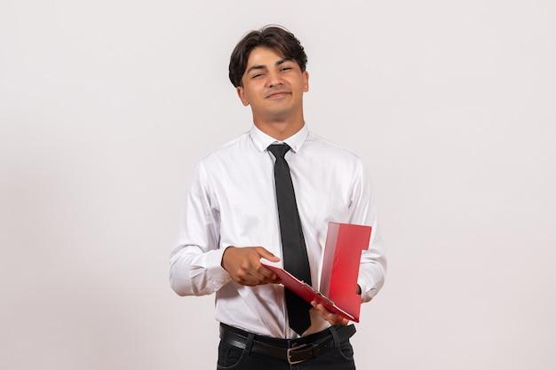 Männlicher büroangestellter der vorderansicht, der rote akte auf weißer wandbüroarbeit menschlicher job hält