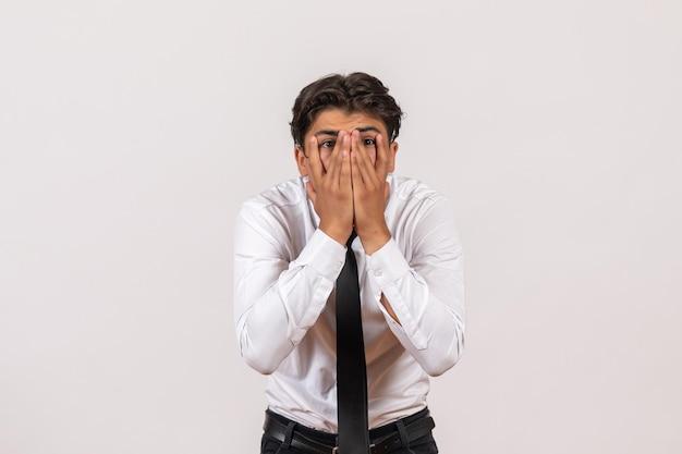 Männlicher büroangestellter der vorderansicht mit schockiertem gesicht auf weißem wandgeschäftsarbeitsjob männlich