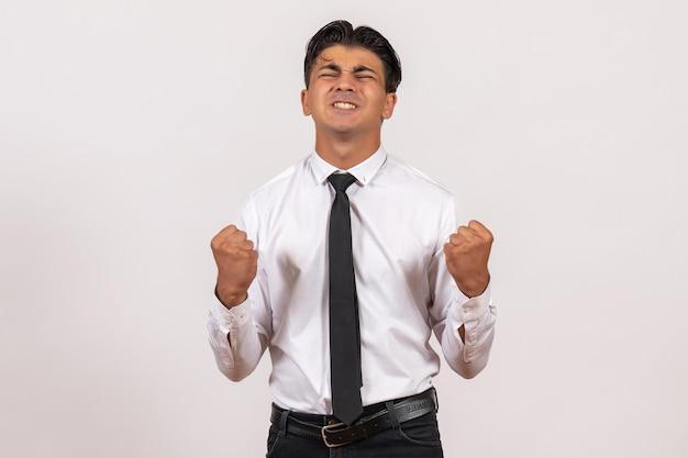 Männlicher büroangestellter der vorderansicht mit starken emotionen auf der weißen wand arbeitet männliches jobgeschäft