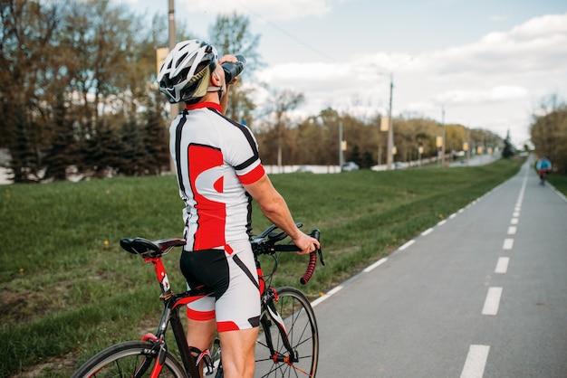 Männlicher bycyclist trinkt wasser während des trainings