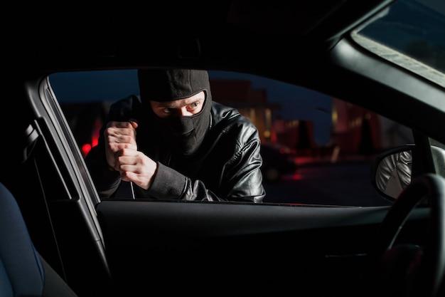Männlicher carjacker mit sturmhaube auf dem kopf, der versucht, autotür mit schraubendreher zu öffnen. dieb entsperren fahrzeug. autotransportkriminalität