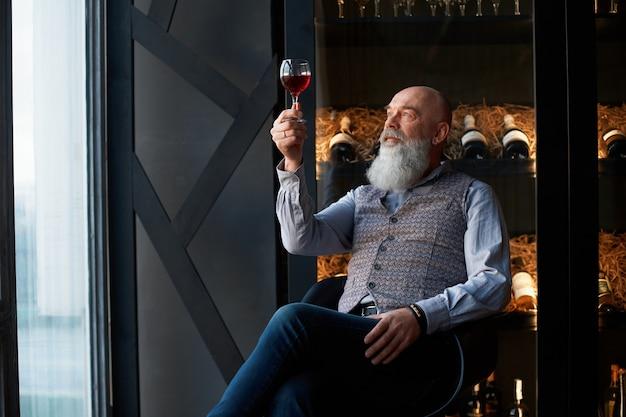 Männlicher cavist, der in einem stuhl sitzt und ein glas wein in der hand betrachtet