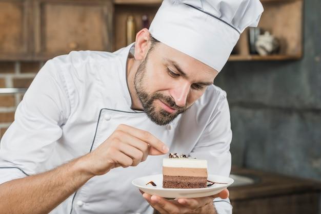 Männlicher chef, der köstlichen nachtisch auf platte verziert