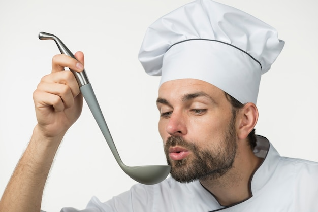 Männlicher chef, der suppe mit schöpflöffel auf weißem hintergrund schmeckt