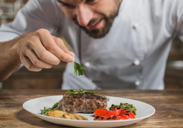 Männlicher chef, der vorbereiteten teller auf küchenarbeitsplatte schmückt