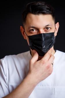 Männlicher chefarzt des arztes in einem weißen op-anzug. nahaufnahmeportrait. trägt eine schwarze medizinische maske gegen das virus