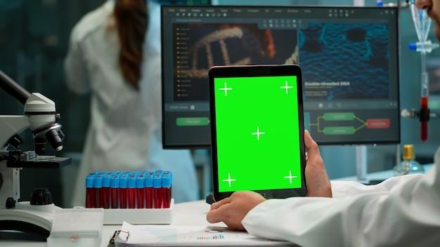 Männlicher chemiker, der eine grüne mock-up-bildschirmtablette am schreibtisch hält. im hintergrund technologieforschung, entwicklungslabor mit facharzt im bereich high-tech-design