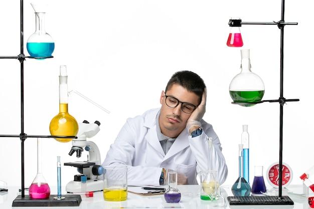 Männlicher chemiker der vorderansicht im medizinischen anzug, der auf hellweißem hintergrundvirus-covid-splash-krankheit wissenschaft sitzt und sich müde fühlt