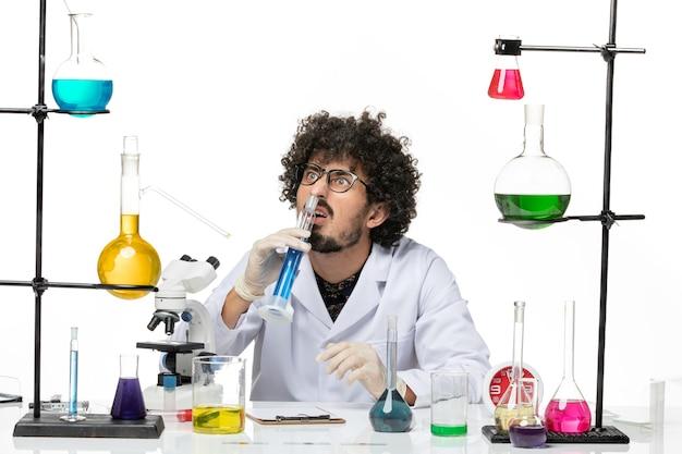 Männlicher chemiker der vorderansicht im medizinischen anzug, der blaue lösung auf weißem raum hält Kostenlose Fotos