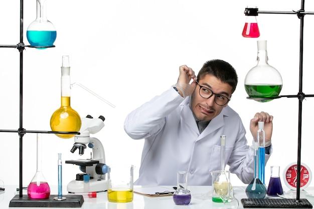 Männlicher chemiker der vorderansicht im medizinischen anzug, der mit lösungen auf der wissenschaft der virus-covid-krankheit des weißen hintergrunds sitzt