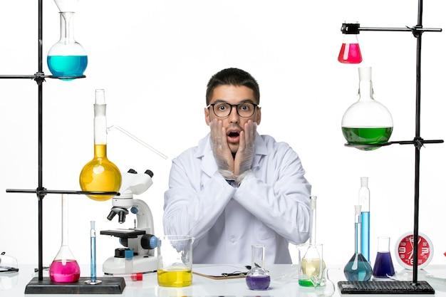 Männlicher chemiker der vorderansicht im medizinischen anzug sitzend mit lösungen auf hellweißem hintergrundvirus covid krankheitswissenschaft