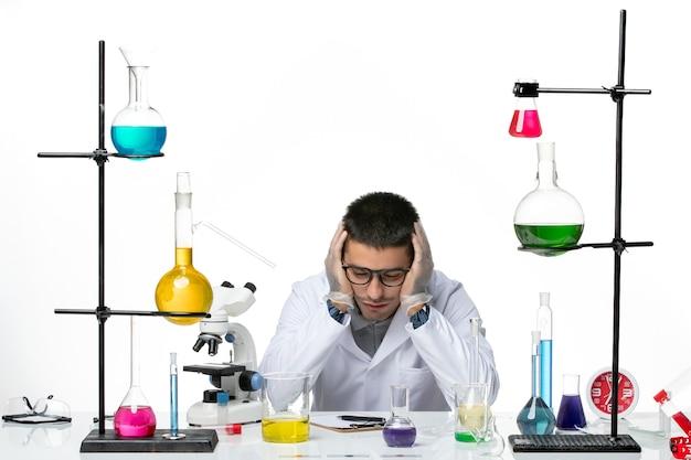 Männlicher chemiker der vorderansicht im medizinischen anzug sitzend und sich müde auf dem weißen hintergrundvirus covid splash disease science