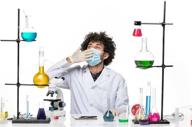 Männlicher chemiker der vorderansicht im medizinischen anzug und mit der maske, die gerade mit lösungen sitzt, die auf weißem raum gähnen