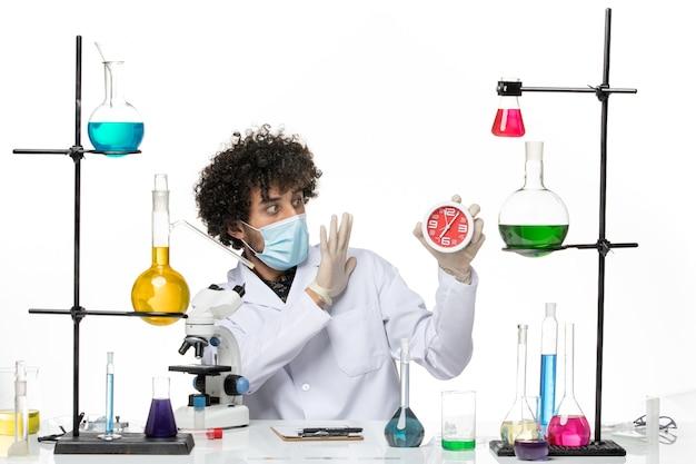 Männlicher chemiker der vorderansicht im medizinischen anzug und mit der maske, die uhr auf hellem weißem raum hält Kostenlose Fotos