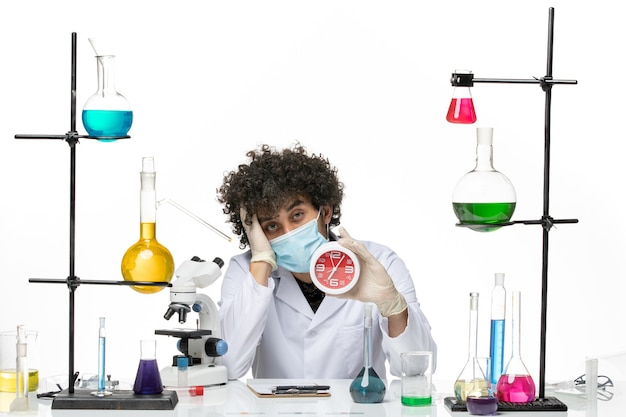 Männlicher chemiker der vorderansicht im medizinischen anzug und mit der maske, die uhr auf hellem weißem raum hält