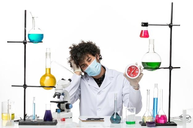 Männlicher chemiker der vorderansicht im medizinischen anzug und mit der maske, die uhr auf weißem raum hält