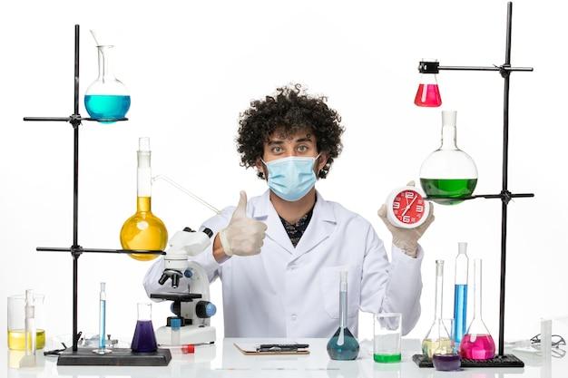Männlicher chemiker der vorderansicht im medizinischen anzug und mit der maske, die uhr auf weißem schreibtisch hält