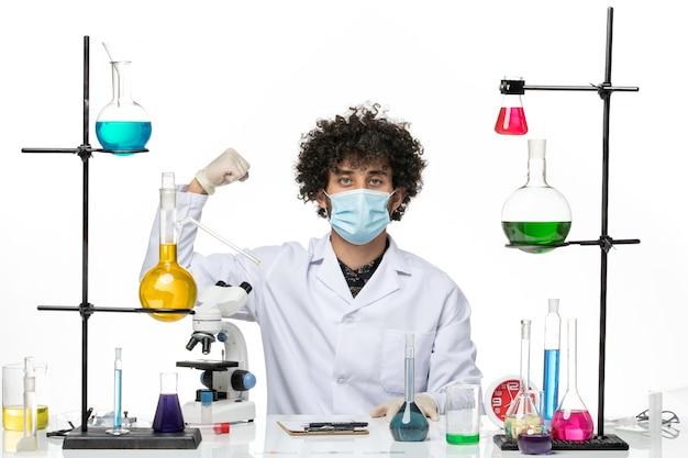 Männlicher chemiker der vorderansicht im medizinischen anzug und mit maske, die gerade mit lösungen sitzt, die auf weißem raum biegen