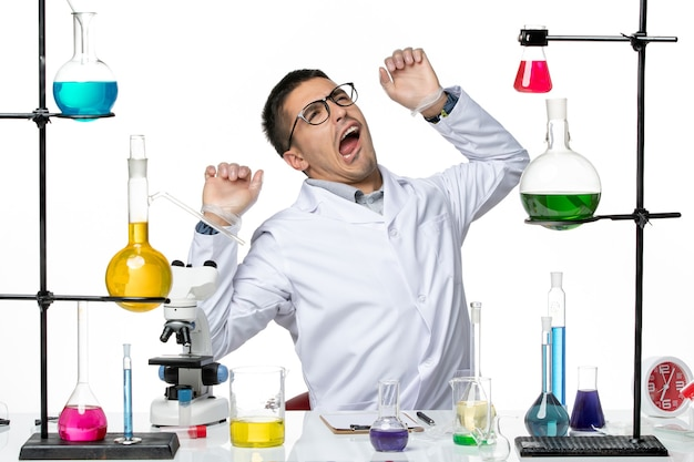 Männlicher chemiker der vorderansicht im weißen medizinischen anzug, der sich auf die arbeit am wissenschaftslabor der weißen hintergrundviruskrankheit vorbereitet