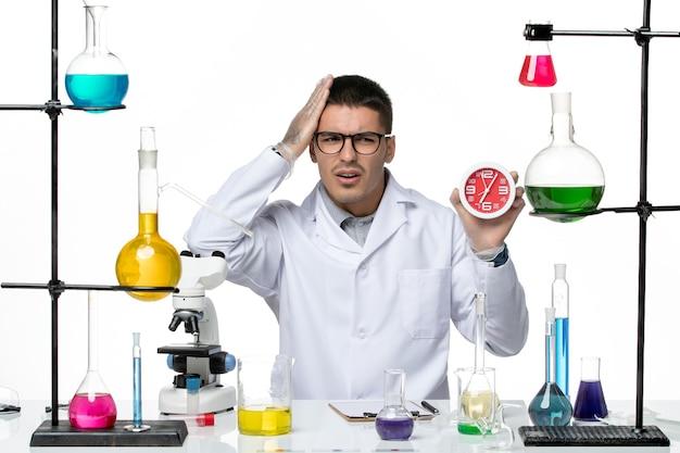 Männlicher chemiker der vorderansicht im weißen medizinischen anzug, der uhren auf wissenschaftslabor der weißen hintergrund-covid-virus-krankheit hält