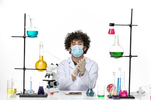 Männlicher chemiker der vorderansicht im weißen medizinischen anzug und mit der maske, die auf leerraum klatscht