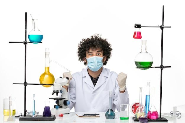 Männlicher chemiker der vorderansicht im weißen medizinischen anzug und mit der maske, die gerade sitzt und sich auf weißem raum freut