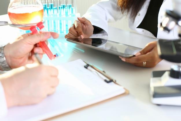 Männlicher chemiker hält reagenzglas aus glas