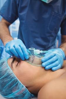 Männlicher chirurg, der eine sauerstoffmaske auf den patienten setzt