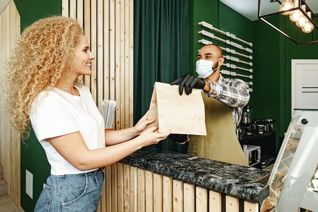 Männlicher coffeeshop-arbeiter, der dem kunden, der gesichtsmaske, coronavirus-konzept trägt, fertige bestellung gibt
