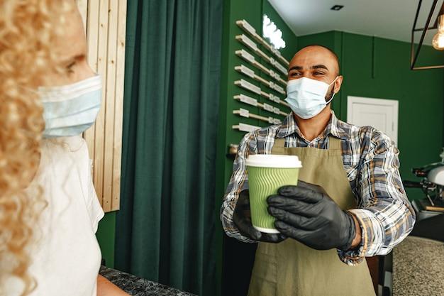 Männlicher coffeeshop-arbeiter, der dem kunden, der gesichtsmaske trägt, fertige bestellung gibt